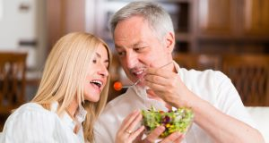 man and woman share a salad