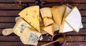 several cheeses on wooden cheese board
