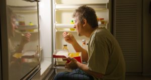 Man eating from refrigerator late at night