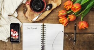 food journal on table with cup of coffee and flowers