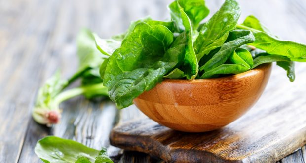 wooden bowl overflowing with fresh spinach
