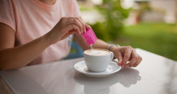 Woman pouring sugar substitute in her coffee