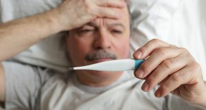 Older man sick in bed taking his temperature