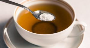 Cup of tea with spoon of sweeter