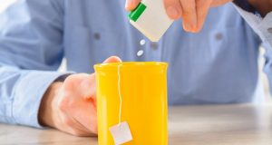 Man putting artificial sweetener in his tea