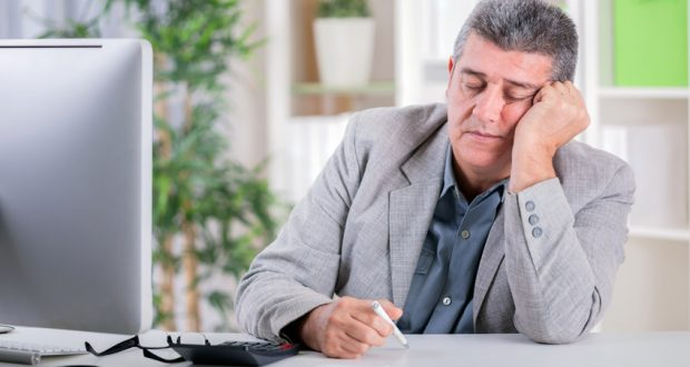 exhausted man sitting in front of computer