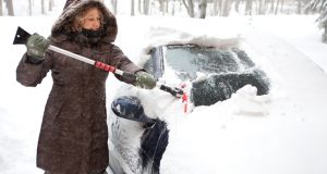 Woman scraping snow off of her car