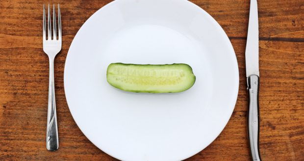 Half a cucumber on a plate with knife and fork