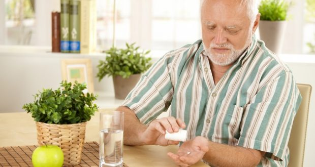 Man taking pill at kitchen table