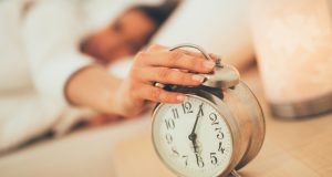 Hand turning off alarm clock