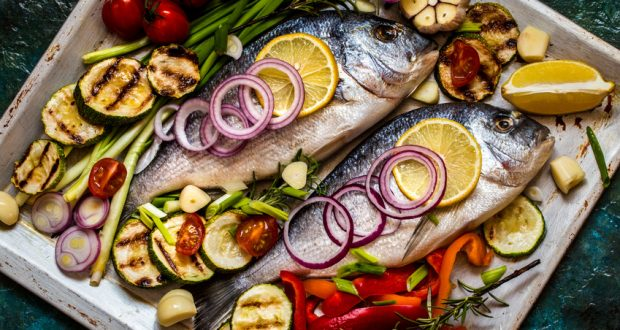 Whole fish baked with veggies and lemon