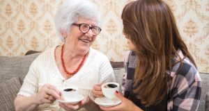 Senior woman drinking coffee with grand-daughter