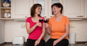 Senior mom and adult daughter drinking red wine together