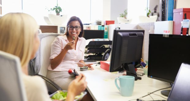 Two women eating healthy snacks at work