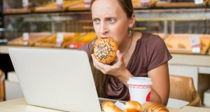 Young woman eating pastry stressed in front of computer