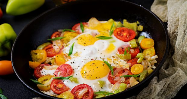 Fried eggs and veggies in cast iron skillet