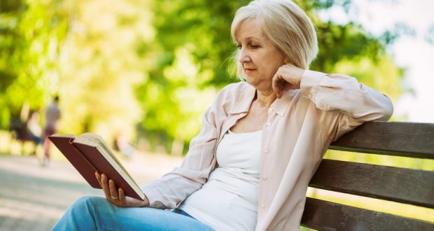 Woman sitting on bench in the park reading a book