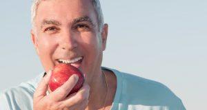 Happy older man eating an apple