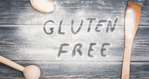 The words gluten free written in flour on wooden table