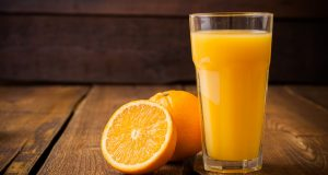 glass of orange juice and fresh orange on wooden table