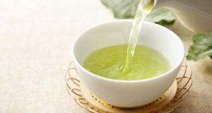 teapot pouring green tea into cup