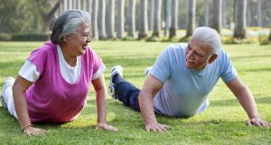 Active older couple exercising in the park