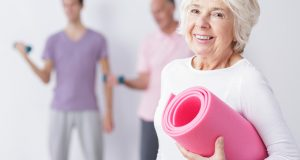 Older woman smiling with yoga mat