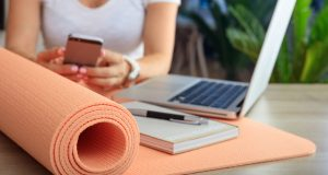 woman with cell phone, laptop, and yoga mat