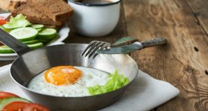 Fried egg in bowl with knife and fork on wooden table