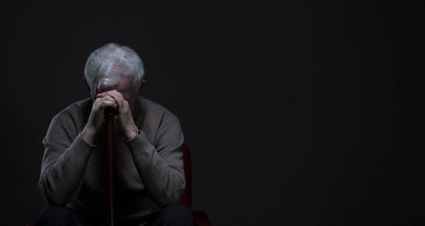 Older man sits alone, appearing depressed