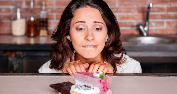 Woman craving piece of cake on a plate