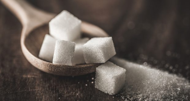 Sugar cubes in wooden spoon