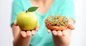 One hand holding an apple the other hand holding a sprinkle doughnut