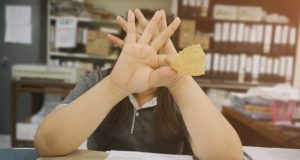 woman eating chips covering her face