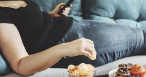 Woman lying on couch eating chips
