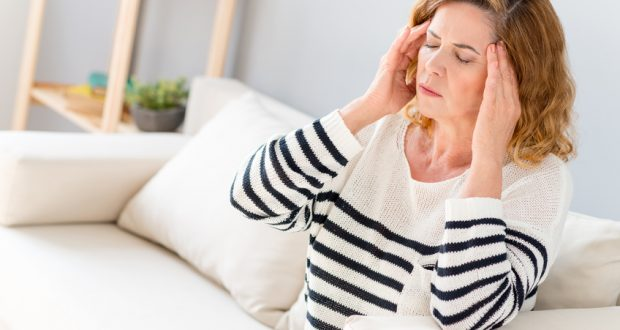 woman with headache sitting on couch